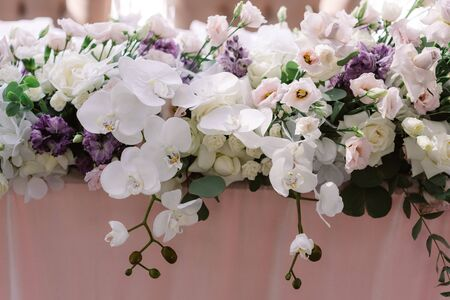 Lots of luxurious fresh flowers on the groom and bride s wedding table. Stylish floristics at a classic wedding