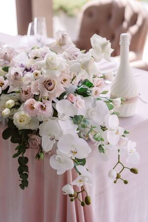 Luxurious flowers on the corner of the wedding table. Stunning white orchids, gentle roses and green eucalyptus twigs