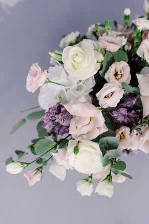 Beautiful fresh flowers on the wedding table. Stylish floristics at a classic wedding on a gray background 스톡 콘텐츠