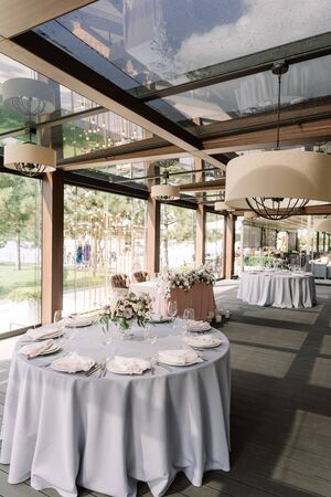 Festive servicing of round tables at the wedding with expensive, clean dishes, bouquets of flowers in glass vases. Gentle flowers, stylish glasses and cutlery stand on a light grey tablecloth