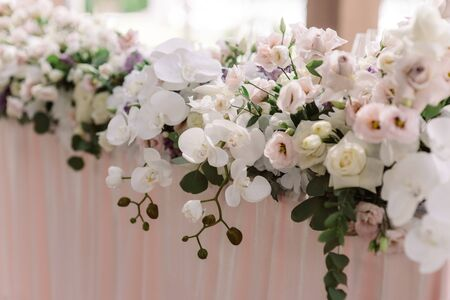 A long composition of fresh luxury flowers on the wedding table of the groom and bride. Decoration of the wedding with flowers in walled tones Reklamní fotografie