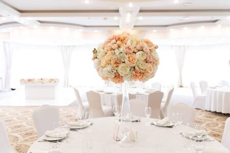 A large wedding bouquet of an assortment of fresh roses of pastel shades adorns the festive table. Stylish floristics at a modern wedding