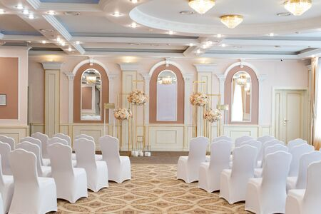Beautiful wedding hall with white chairs for guests. Bright and stylish decoration. Wedding flowers on stands Stock Photo