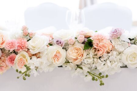 A beautiful bouquet on an elongated wedding table made of roses of different shades. Luxurious fresh flowers on a white background