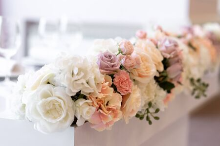 Lovely floral design on the groom and bride s desk. Roses and cloves on the white table Stock fotó