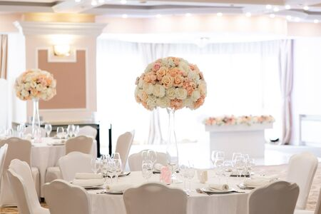 Flower decor on white round tables for a torched reception in the reception. Large flowers compositions on high glass vases