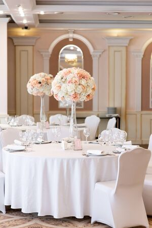 Luxurious wedding decor at the dining tables in the restaurant s bright hall. Art decoration of the wedding with fresh flowers