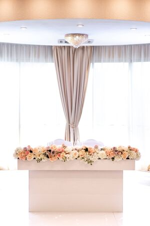 Variety of shades and varieties of roses in stylish decoration of the table of newlyweds. Luxury white groom and bride table stands near window