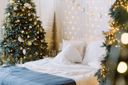 Stylish Christmas interior with a soft bed. Christmas tree with presents underneath in living room Stock Photo