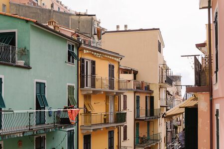 Wooden shutters on a bright Italian houses. Balconies and a narrow Italian street