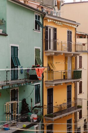 Narrow balconies in the old town of Manarola. Italian houses and narrow balconies. Wooden shutters on a bright Italian houses