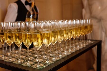 Lots of champagne glasses. Alcoholic drinks at the event. Sparkling drink. Champagne into a glasses on a festive event