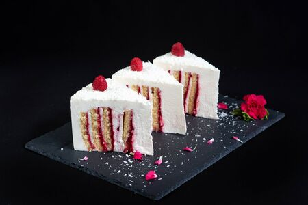 Elegant Cake with coconut and raspberry covered with chocolate glaze. Slice of white layered cake on isolated black background. Wallpaper for pastry cafe or cafe menu. Horizontal. Foto de archivo - 137896147