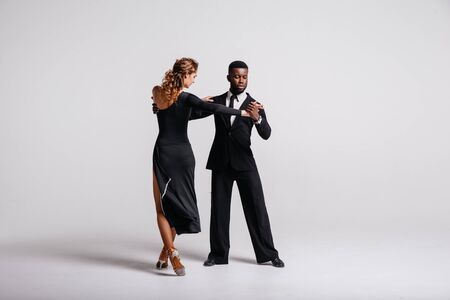 Couple dancers posing over white