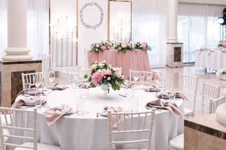 The luxurious round table for the wedding lunch is decorated with flowers and stylish dishes. Beautifully organized event - served festive tables ready for guests Foto de archivo