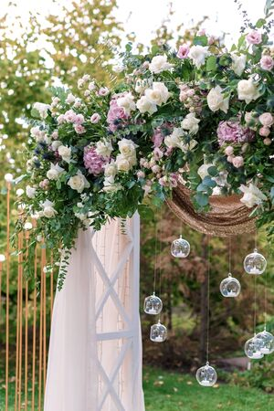 Arch for the wedding ceremony, decorated with cloth and flowers. Luxury reception