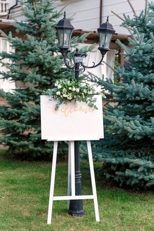 Wedding white Board Mockup easel with welcome sign decorataed with flowers, outdoors. Greeting card template