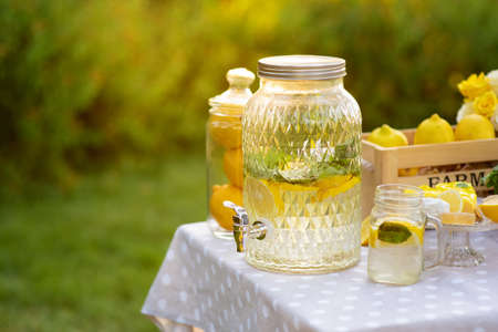 Big jar with lemonade outdoors. Mint and yellow lemons. Copy space. The concept summer relax and picnic. Healthy Food and Drink.