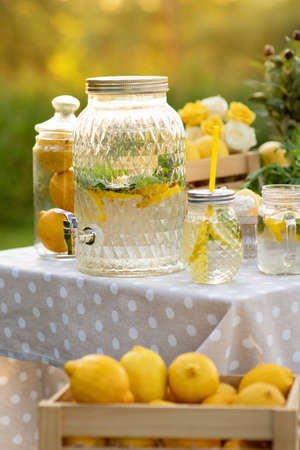 Big jar with lemonade outdoors. Copy space. The concept summer relax and harvest. Wooden box with lemons. Healthy Food and Drink.