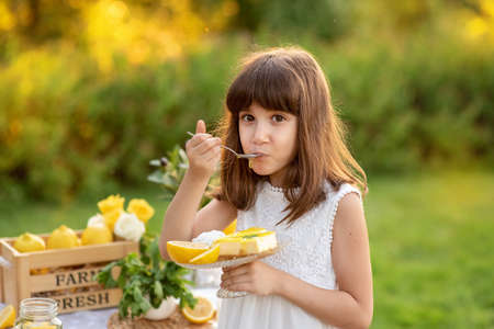 Girl eating lemon Birthday cake. Lemonade birthday party at summer park. Food, celebration and festive concept. Archivio Fotografico