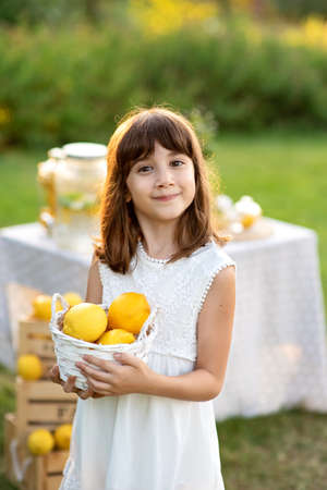 Smiling girl holding bowl of lemons. Harvesting festing party. Vitamins and healthy food. Useful citrus fruits as prevention of viral and respiratory diseases. 스톡 콘텐츠