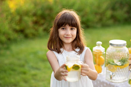 Summer refreshing natural drink lemonade. Little girl drink natural lemonade at stand in park.
