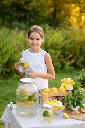 Cute little children selling lemonade in park. Lemons, mint, cocktail cans in boxes for lemonade close-up. Homemade lemonade in dispenser and copy space.