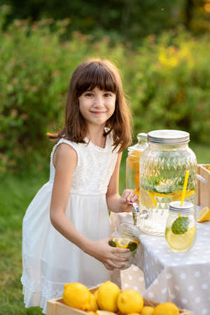 Girl sells homemade lemonade close-up and copy space. The girl in the summer makes homemade lemonade. Detox fruit infused flavored water, cocktail in a beverage dispenser with fresh fruits