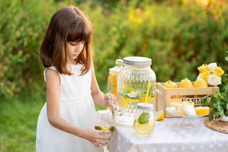 Girl in the summer makes homemade lemonade. Detox fruit infused flavored water, cocktail in a beverage dispenser with fresh fruits