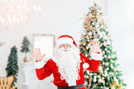 Happy Santa Claus indoors near christmas tree carrying no gifts to children