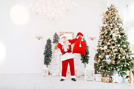 Happy Santa Claus with a bag full of presents indoors near christmas tree