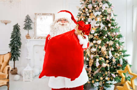 Happy Santa Claus indoors near christmas tree carrying gifts to children