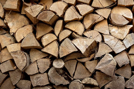 Stacks of firewood in the sawmill. Storage of wood. Firewood background 스톡 콘텐츠
