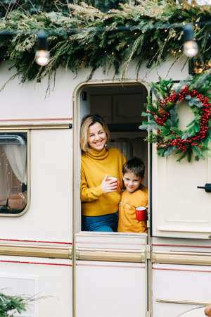 Beautiful mother and child boy with red cups drink cocoa or tea in trailer. Family vacation RV holiday trip, happy smiling family travel on camper, people in motorhome interior. Caravan in park