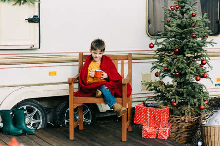 Child boy with red cups drink cocoa or tea in trailer. Family vacation RV holiday trip, happy smiling family travel on camper, people in motorhome interior. Caravan in park