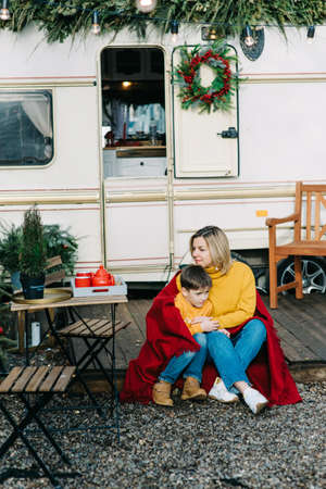 Beautiful mother and child boy with red plaid sitting near trailer. Family vacation RV holiday trip, happy smiling family travel on camper, people in motorhome interior. Caravan in park 스톡 콘텐츠