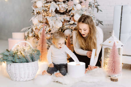 Blond Hair Young Boy and blond pretty woman enjoying Christmas Time opening gifts under Christmas tree 스톡 콘텐츠