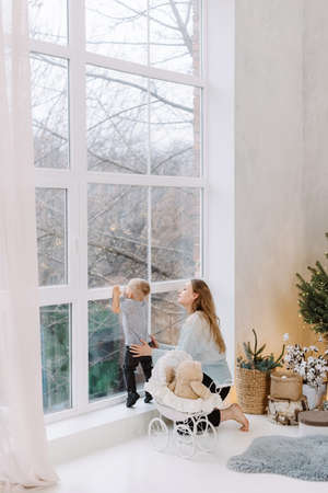Merry Christmas and Happy Holidays! Woman and blond toddler boy looking in window near Christmas tree indoors. The morning before Xmas. Waiting for Santa Claus and miracle