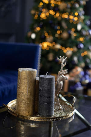 Luxurious decoration of the house by Christmas. Brilliant cylinder-shaped candles. Romantic decor home to New Year s Eve. New Years stylish candles 스톡 콘텐츠