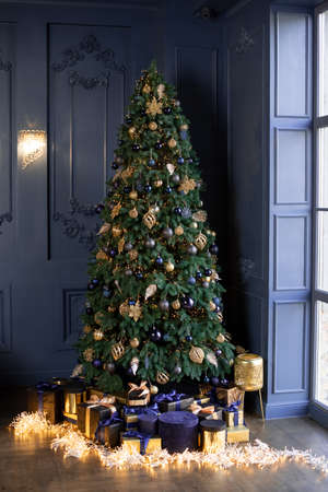 A large tall spruce in the corner of the room with designer decoration and against a dark wall. Luxurious modern decor for Christmas