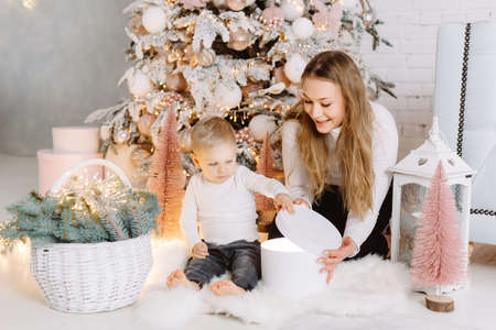 Blond Hair Young Boy and pretty woman enjoying Christmas Time opening gifts under Christmas tree