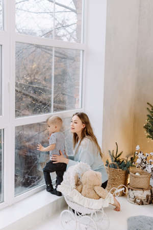 Merry Christmas and Happy Holidays! Woman and blond toddler boy looking in window near Christmas tree indoors. The morning before Xmas. Portrait loving family close up.