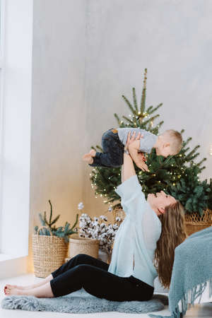 Happy blond hadsome boy and pretty woman playing under Christmas tree in cosy scandinavian interior 스톡 콘텐츠
