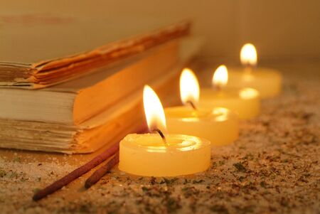 witchery: Esoteric atmosphere created with candles, old books and incense  Stock Photo