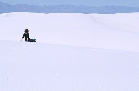 Rear view of a woman sitting alone on White Sands National Monument, New Mexico, USA photo