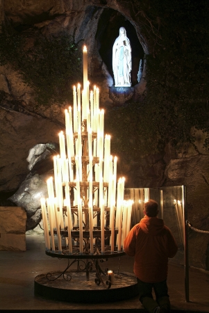 pyrenees: Man praying at the Grotto of Lourdes, in France, at night