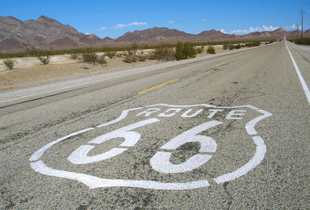long road with a Route 66 sign painted  photo