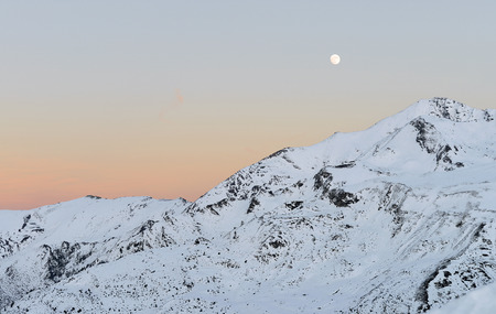 Landscape of snowy mountains at sunset, with the full moon