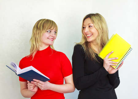 two beautiful young girl with long blond hair are holding a book and notebook, look at each other, smiling Stock Photo - 9315021