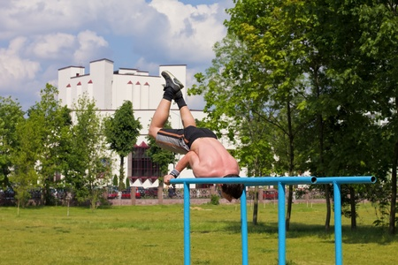Teen doing gymnastics on the uneven bars at the park during the summer Stock Photo - 13993100